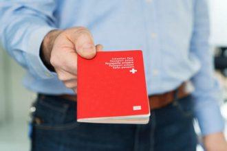 Ein Mann haelt einen biometrischen Schweizer Pass in der Hand, aufgenommen am 10. Februar 2014 in Bern. (KEYSTONE/Christian Beutler)  A man holds a Swiss biometric passport, pictured in Bern, Switzerland, February 10, 2014. (KEYSTONE/Christian Beutler)